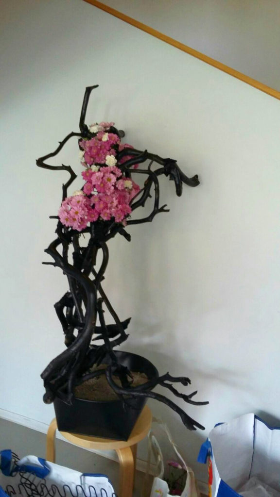 Pine branches painted black with pink flowers